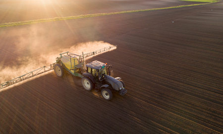 Aerial image of tractor spraying soil and young crop in springtime in field 版權商用圖片