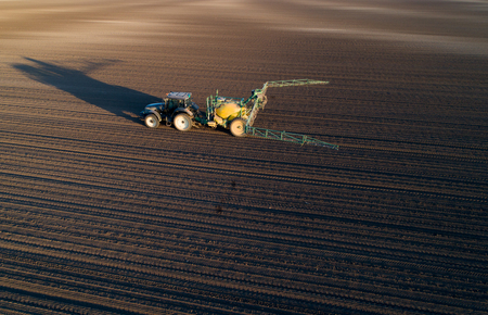 Aerial image of tractor with spraying equipment driving on field with young crop in springtime