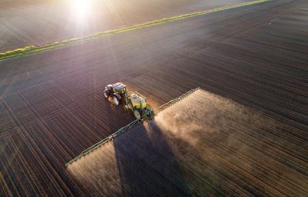 Aerial image of tractor spraying soil and young crop in springtime in field Stok Fotoğraf