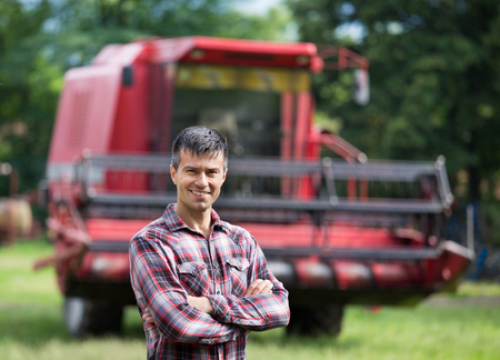 Confident handsome farmer standing with crossed arms in front of combine harvester on farm