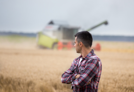 Handsome farmer with crossed arms standing in front of combine harvester during harvest in field