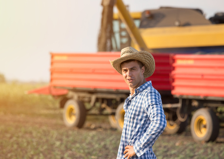 Handsome farmer with straw standing in front of combine harvester and trailers during harvest 스톡 콘텐츠