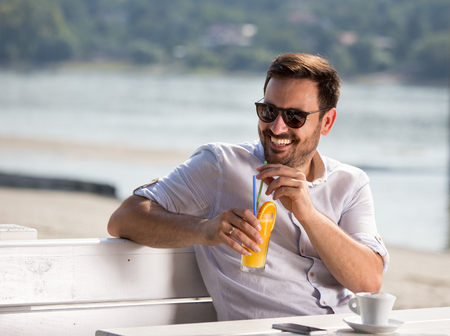 Handsome man drinking orange juice and enjoying morning in cafe on river sand beach
