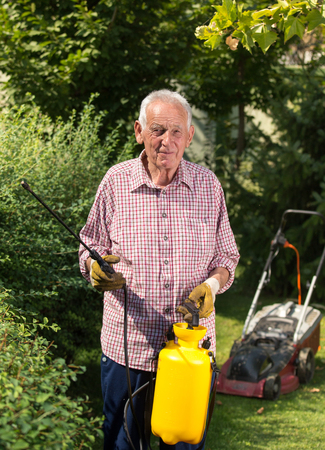 Senior man spraying hedge in garden.  Mower in background. Taking care of plants concept Archivio Fotografico