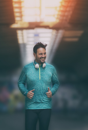 Satisfied handsome man running under bridge. Urban morning jogging Stok Fotoğraf