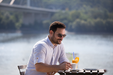 Handsome man drinking coffee and orange juice in cafe on river beach in morning Banco de Imagens