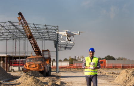 Happy engineer controlling drone above building site with metal construction and crane in background