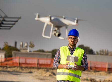 Portrait of engineer with helmet operating with drone on remote control at building site