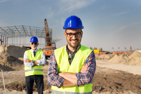Portrait of satisfied and confident engineer with helmet and vest on building site