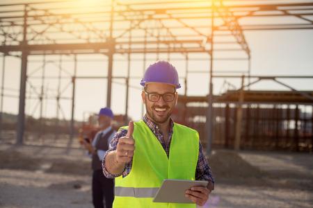 Porträt eines zufriedenen Ingenieurs, der Tablet hält und Daumen auf der Baustelle zeigt Standard-Bild