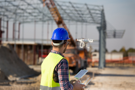 Rear view of engineer controlling drone above building site with metal construction and crane in background 写真素材