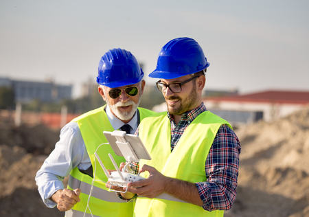 Two engineers with helmets and vests operating with drone by remote control. Technology innovations in construction industry