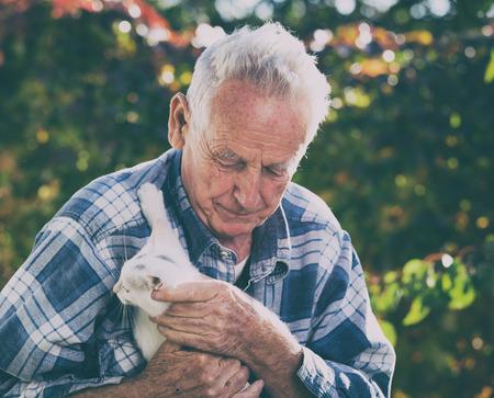 Senior man with little white cat in garden