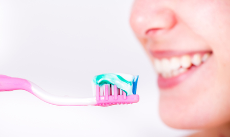 Close up of toothbrush with paste and smiling woman with white teeth in background