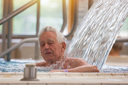 Elderly man enjoying in pool with hot water and massaging shower in spa resort