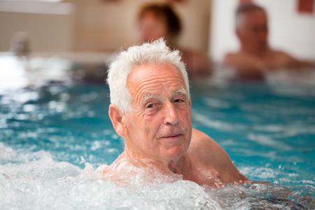 Elderly man enjoying in pool with hot water in spa resort