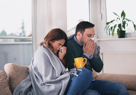 Young couple sitting on sofa covered with blanket, sneezing and blowing nose. Cold and flu season