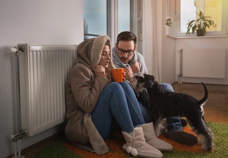 Pareja joven en chaqueta y cubierto con una manta sentados en el suelo junto al radiador con perro y tratando de calentar