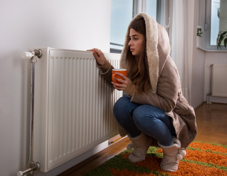 Young woman in jacket squatting beside cold radiator and drinking tea Stock fotó