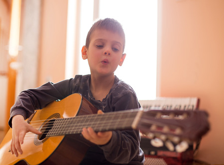 Cute little boy sitting on floor, playing guitar and whistling
