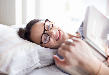 Pretty girl with glasses reading book in bed in morning