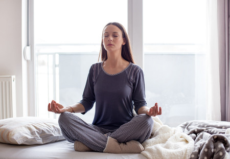 Pretty young girl doing yoga and meditation poses on bed in morning Stock Photo