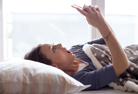 Girl in bed looking at mobile phone with chocked and panic face expression. Oversleep and getting late concept
