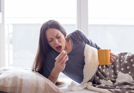Girl lying in bed holding cup of tea and sneezing. Virus or flu concept