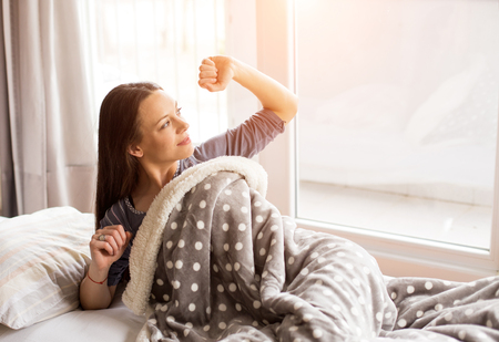 Pretty young woman waking up and stretching in bed beside window Stock Photo