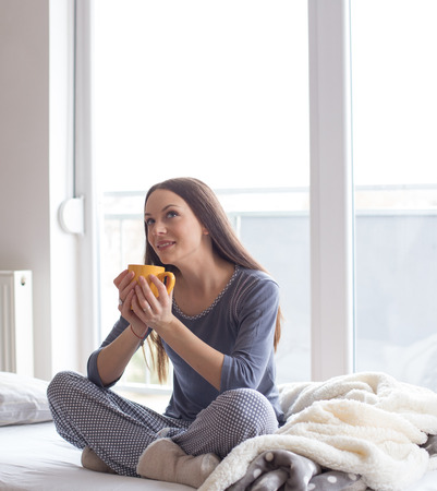 Beautiful woman sitting in bed beside window, holding cup of hot coffee and daydreaming