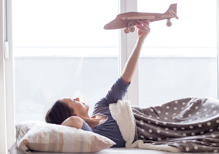 Happy young woman lying in bed and holding wooden airplane toy in air and daydreaming
