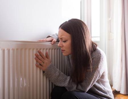Girl squatting beside radiator and trying to warm up Stock Photo