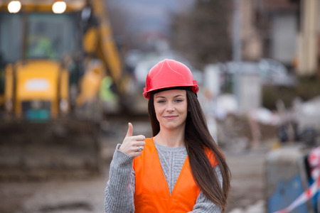 Young woman engineer with helmet showing thumb up as ok sign in front of excavator at construction site Stock Photo