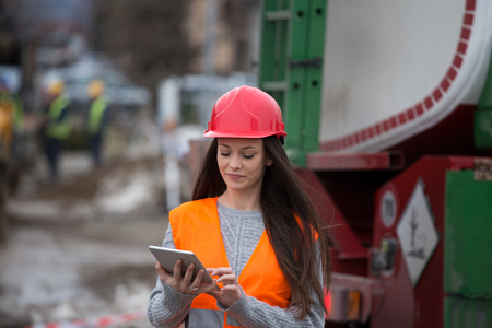 Pretty young woman engineer with tablet standing at construction site Stock Photo