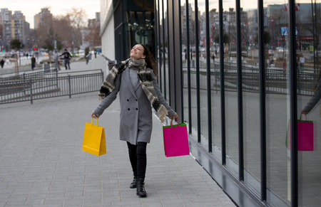 Excited young woman with shopping bags walking in front of mall