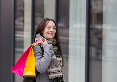Happy shopaholic girl with shopping bags standing in front of fashion mall Stock Photo