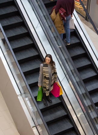 Happy girl with shopping bags on escalator of mall