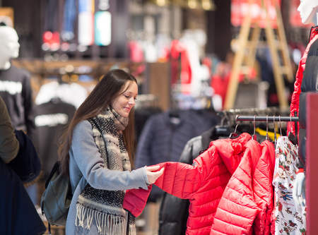 Pretty young woman choosing clothes in store