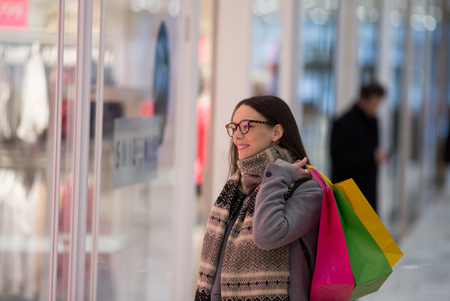 Happy shopaholic girl with shopping bags standing in front of store window and looking clothes
