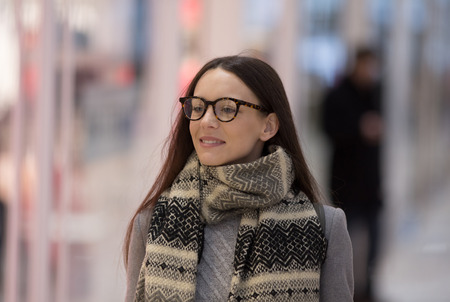 Portrait of pretty young woman in coat walking in shopping mall
