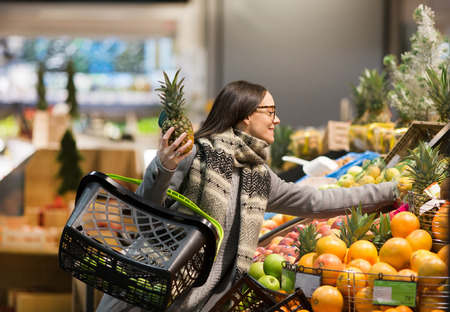 Pretty woman buying fresh tropical fruits in store