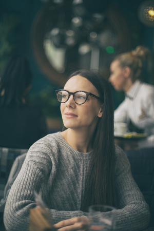 Portrait of pretty young woman in cafe, looking through window and waiting for someone