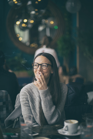 Girl sitting in cafe drinking coffee, smoking cigarette and talking to a friend