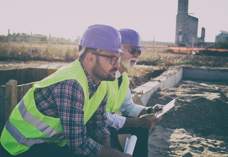 Young and senior engineer sitting at building site and thinking about problems in construction