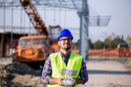 Young engineer controlling drone above building site with metal construction and crane in background