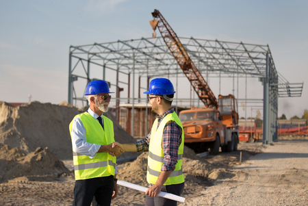 Two engineers shaking hand on building site with metal construction in background