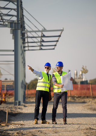 Two engineers with helmets and vests talking at building site in front of metal construction