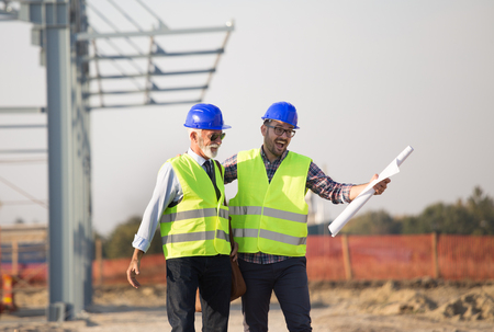 Two enthusiastic engineers with helmets and vests talking at building site in front of metal construction Stock Photo