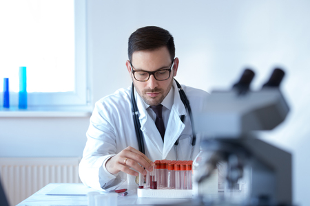 Young attractive doctor with blood samples sitting in laboratory Stock Photo