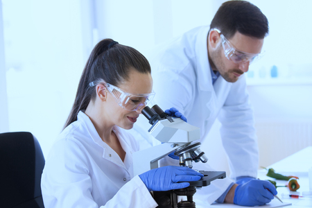 Two scientists researching vegetables in lab with microscope